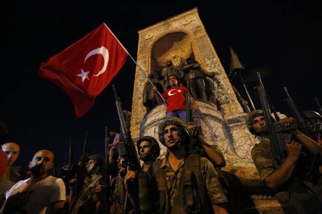 トルコ・イスタンブールの中心地タクスィム広場でクーデター未遂事件の翌日、トルコ国旗が振られるなか、周囲を見張るトルコ軍=2016年7月16日