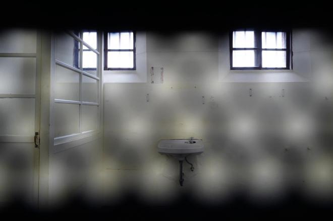 監視窓から見える雑居房(定員3人、広さ約9㎡)内の様子。左端の仕切りの中がトイレ=2017年7月、矢木隆晴撮影