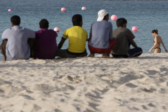ドバイのビーチにたたずむ男性たち(記事本文とは関係ありません)=2007年12月2日
