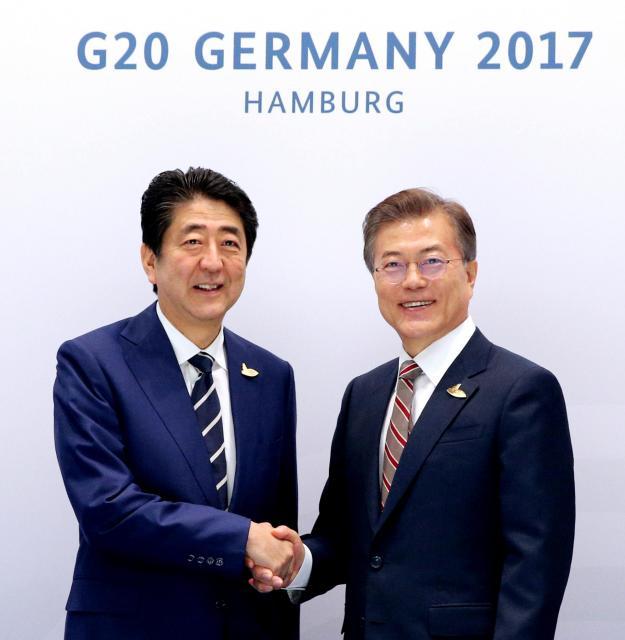 G20(主要20カ国・地域)首脳会議に合わせた会談を前に、韓国の文在寅大統領(右)と握手する安倍晋三首相=7月7日、独ハンブルク