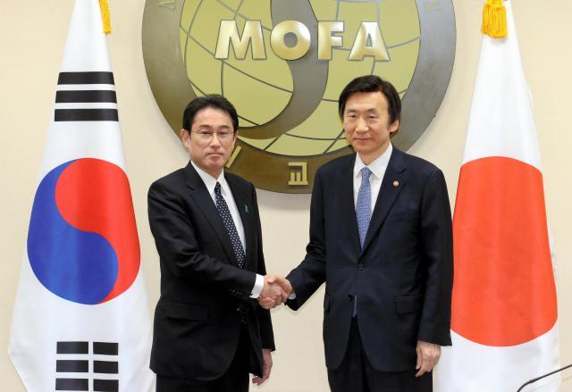 握手する岸田文雄外相(左)と韓国の尹炳世外相。この後の会談で慰安婦問題の「最終的かつ不可逆的解決」に合意した=2015年12月28日、ソウル