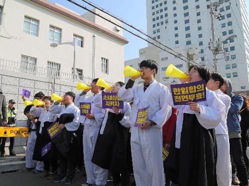 韓国・釜山の日本総領事館前で、慰安婦問題の日韓合意の無効などを訴えてデモする人たち=2017年3月、東岡徹撮影