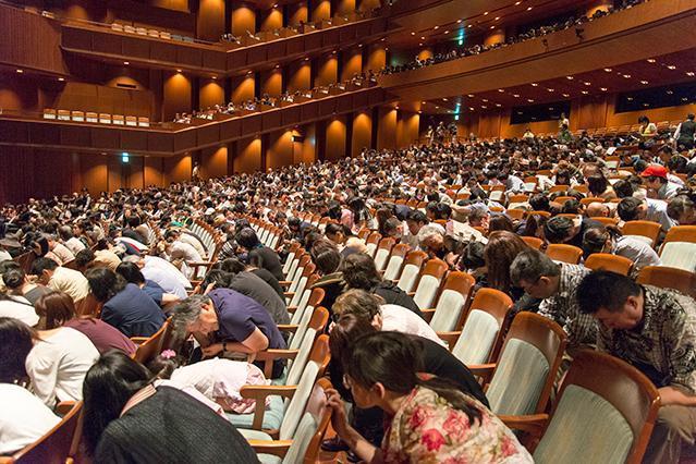オペラの途中で「地震発生」。その場で身を守る訓練をする観客=新国立劇場提供