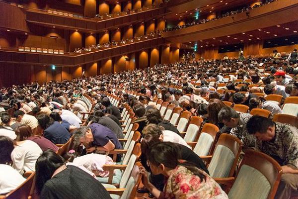 オペラの途中で「地震発生」。その場で身を守る訓練をする観客=2014年、新国立劇場