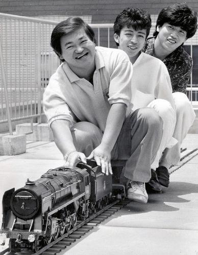 ハドソン社員と模型機関車に乗って楽しむ高橋名人(手前)=1987年6月28日