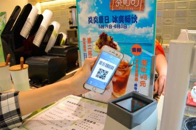 アリペイの支払いに対応する飲料品店では、スマホに表示した2次元バーコードを機器にかざすと支払いが済ませられる=2016年5月20日、北京市内