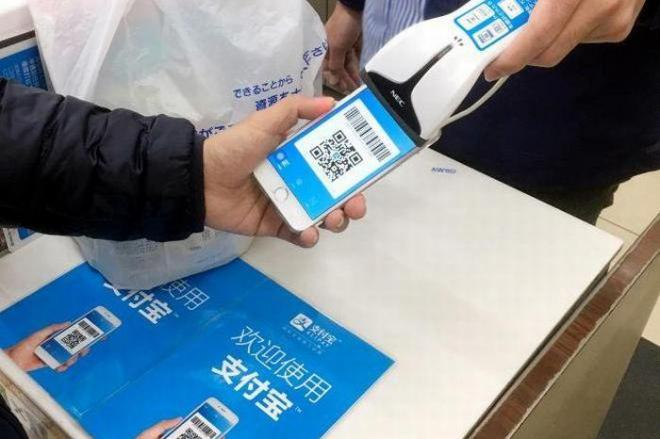アリペイを使ったローソンでの支払い。スマホのアプリで2次元バーコードを表示させ、店側が読み取ると支払いが完了する=東京都内の店舗、ローソン提供