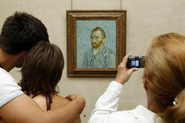 ゴッホの自画像を撮影する女性=ロイター