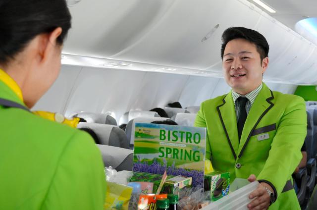 機内販売のサービスをする春秋航空日本の男性客室乗務員(右)