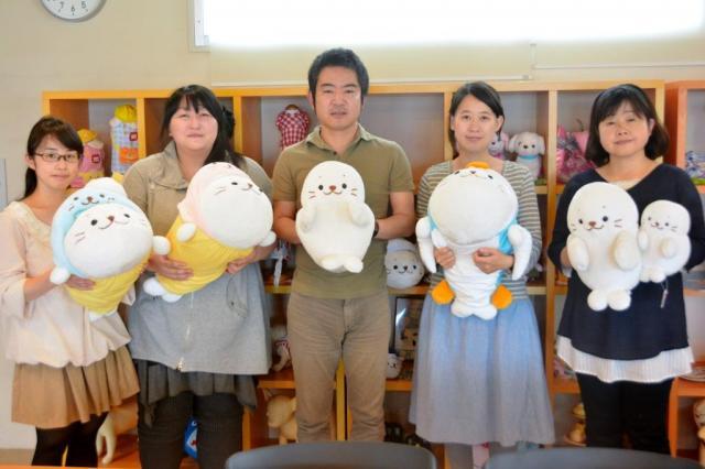 しろたんグッズの企画責任者を務める横山健一さん(右から3人目)らデザイナーやディレクター=長野市
