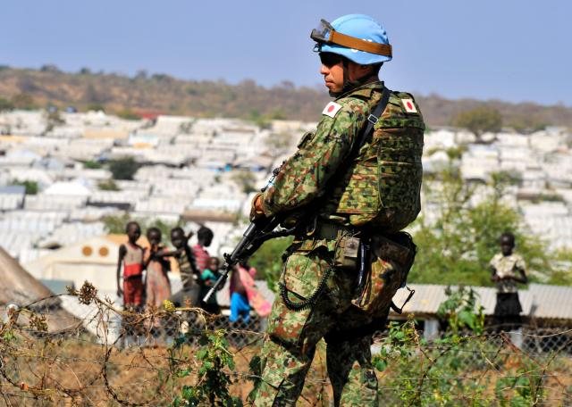 南スーダンPKOに参加し、小銃を手に警戒する陸上自衛隊員。周辺(奥)では施設部隊による国内避難民保護区での防護壁工事が続く。施設部隊は今年5月まで派遣された=16年11月、ジュバ