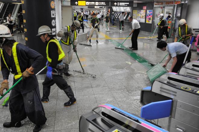 ゲリラ豪雨に見舞われた東京・渋谷の地下構内で水をはき出す駅職員ら=2015年7月、渋谷駅