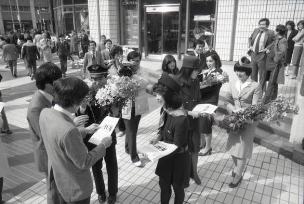 【1984年】歴代の6種類のユニホームを着た日本航空の客室乗務員が春を告げる沖縄直送のスプレー菊なでしこ1000本を道行く人に手渡した