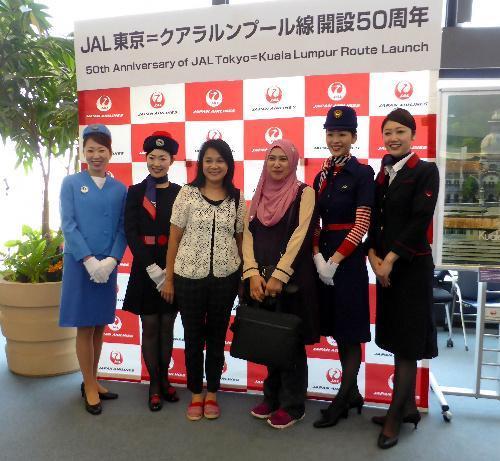 乗客と記念写真に納まる、歴代の制服を着たJALの客室乗務員=2017年5月、成田空港