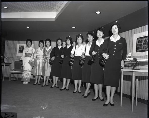 【1960年】新制服を着る客室乗務員たち。(右から二人ずつ)制服と制帽、夏用の上着なし、外とう姿、サービング・コート。左端の一人は和服姿
