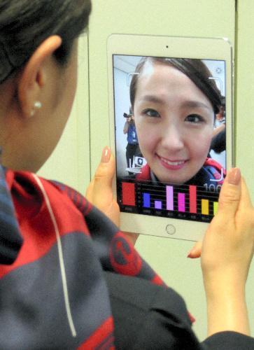 【2016年】資生堂のアプリを使って笑顔を確認する日本航空の客室乗務員=東京都港区