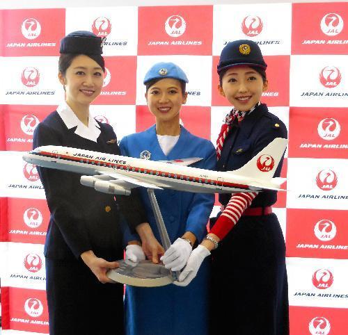 歴代の制服を着用したJALの客室乗務員。左より就航当時の3代目、4代目、6代目。手にしている模型はダグラスDC―8型機=2016年11月、成田空港