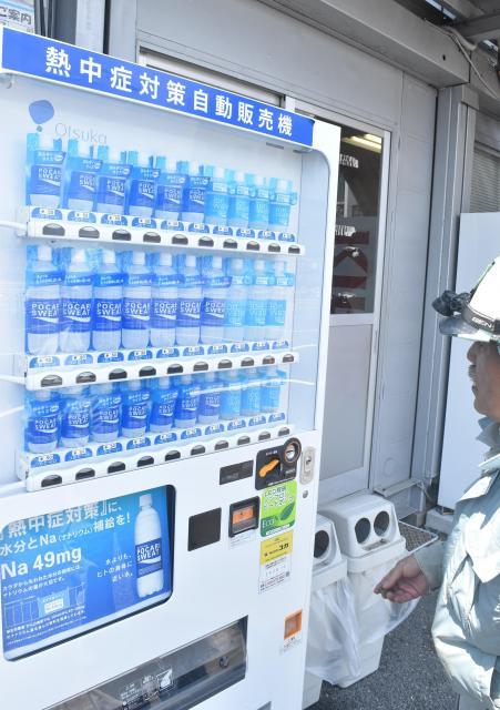 「熱中症対策」としてポカリスエットなどが50円で販売されている自販機=川崎市