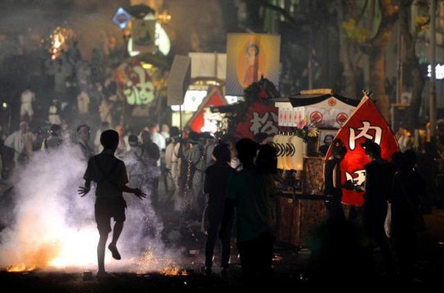 激しい爆竹の音の中、家族らに引かれた精霊船が練り歩く精霊流し=2013年、長崎市