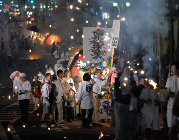 【2013年の精霊流し】爆竹の煙と火薬のにおいに包まれて、家族らにひかれた精霊船が街中を練り歩いた=長崎市