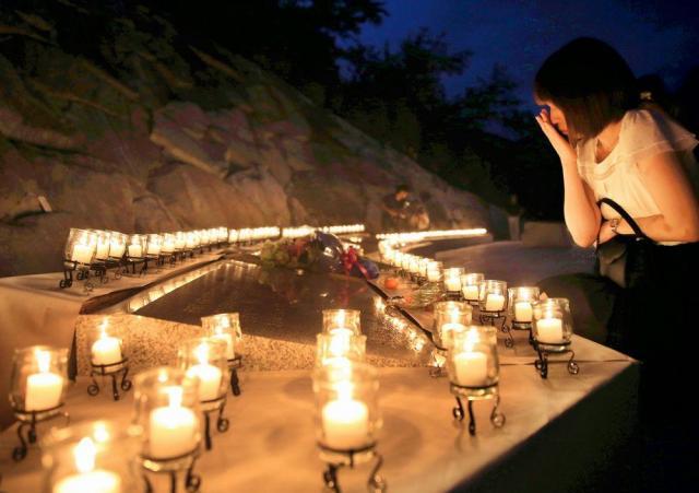 犠牲となった520人の名前が書かれた銘板を見つめる女性=2015年8月12日