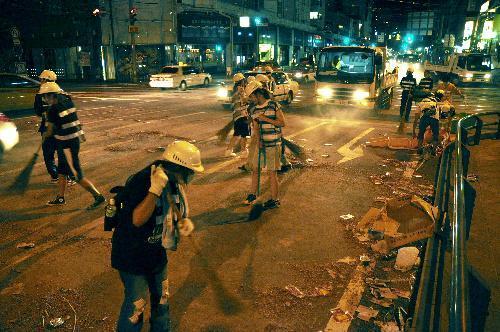 【2012年の精霊流し】精霊流しの終了直後から路上に散らばった爆竹を片付ける人たち=長崎市