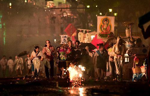 【2014年の精霊流し】故人の魂を乗せた精霊船を引き坂を上る人たち=長崎市