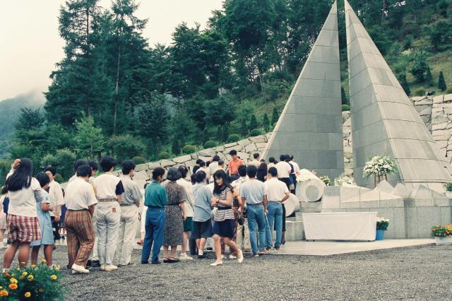 日航機墜落事故追悼7周年の慰霊式典で手を合わせる遺族たち