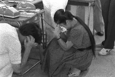 「もしもし、まだわかんないのよ……」と話しているうちに泣き崩れる女性。かたわらの男性も話しながら大粒の涙を浮かべて下を向いた=1985年8月15日