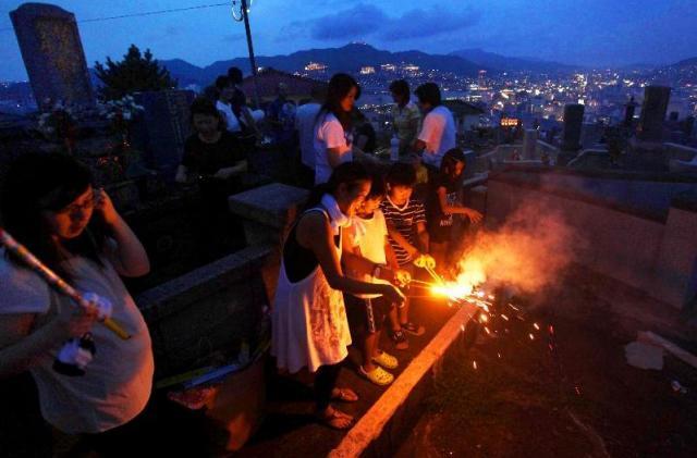 お墓の前で花火をする人たち=2009年8月14日、長崎市