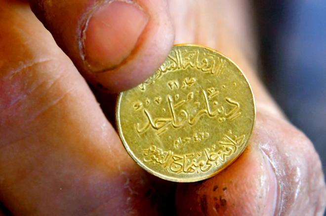 イスラム国(IS)がつくった金貨。上部に「イスラム国」、中央に「21カラット 1ディナール 4.25グラム」、下部に「カリフの統治は預言者の道」などと書かれている。モスル市内の貴金属店で見せてもらった=2017年5月31日、仙波理撮影