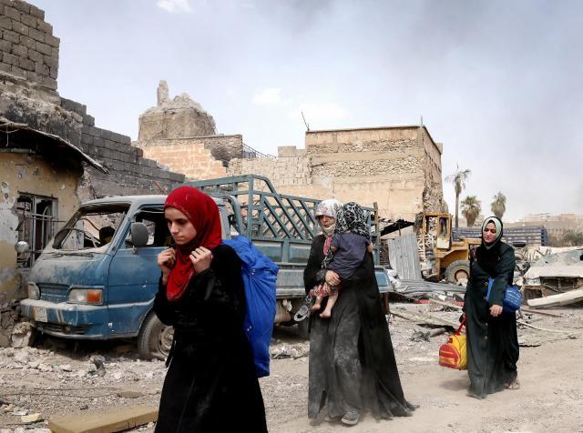 ISに爆破されたモスルのヌーリ・モスク脇を通って避難する住民=2017年7月2日、杉本康弘撮影