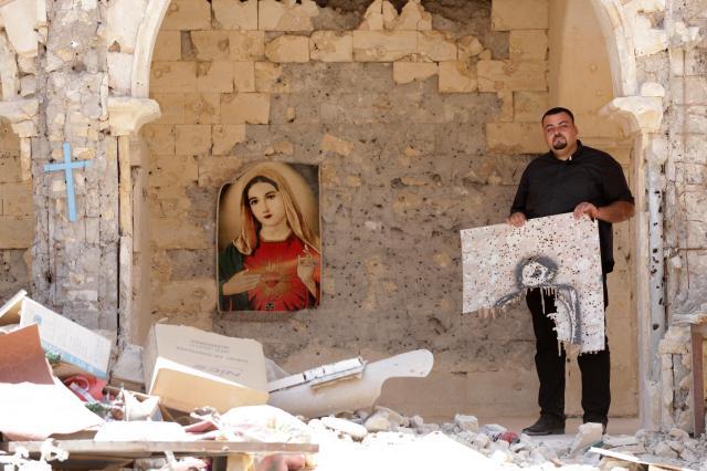 ISが射撃の練習に使っていたカラコシュの教会の中庭に立つマジード・アタラ神父。手にした板や壁に、銃弾の穴が無数に開いていた=2017年6月29日、杉本康弘撮影