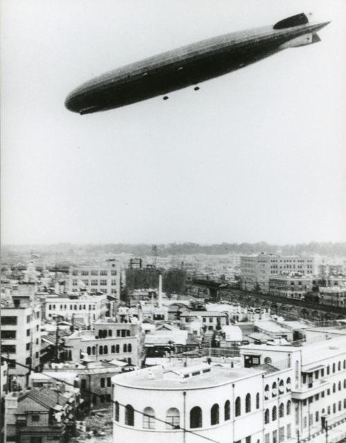 日本に飛来し東京上空を飛行するドイツの飛行船グラフ・ツェッペリン号。手前の白い建物は泰明小学校=1929年8月19日