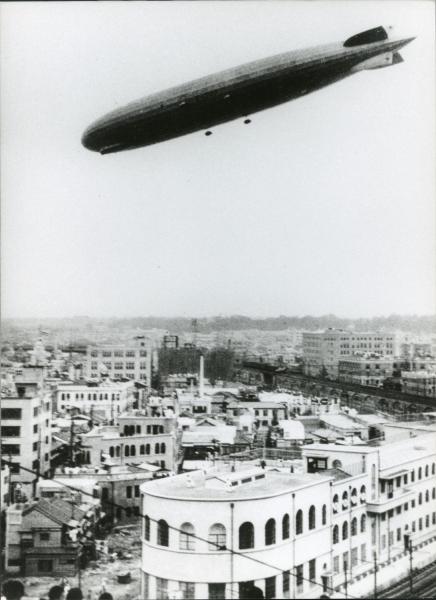 日本に飛来し東京上空を飛行するツェッペリン伯号。手前の白い建物は泰明小学校=1929年8月19日