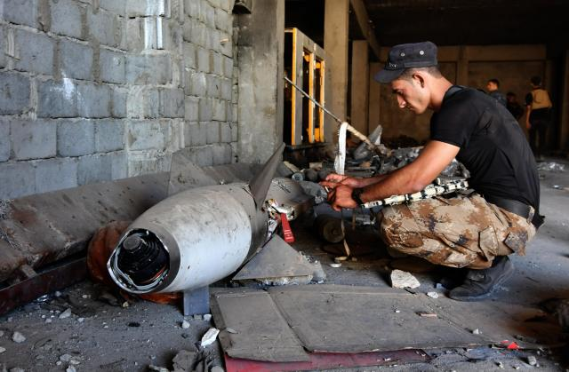 ISの武器工場に残された、航空機搭載型ミサイルとみられる不発弾を調べるイラク兵=2017年5月24日、仙波理撮影