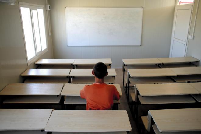 IS支配下のモスルで、ISの教育を受けさせられた10代の少年。避難先のイラク北部アルビル郊外のキャンプ内にある学校で、後ろ姿だけの撮影に応じた=2017年6月16日、杉本康弘撮影