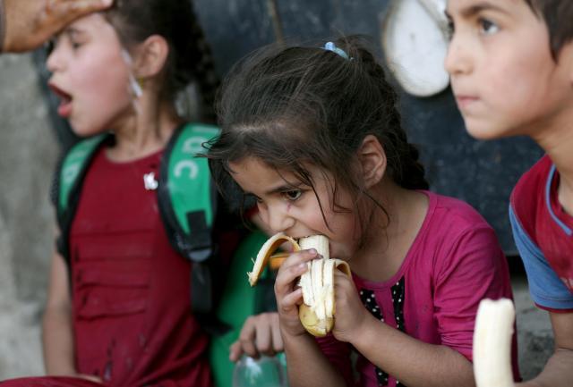 モスルでISの支配下から救出された子どもたち。配給されたバナナに夢中でかぶりついた=2017年6月23日、杉本康弘撮影