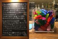 長崎市内にある「みらい長崎ココウォーク店」に設置された黒板メッセージ(左)と、寄せられた折り鶴