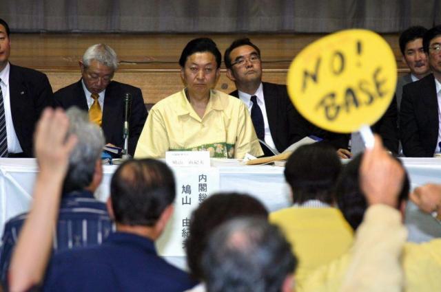 鳩山由紀夫首相(当時)へ質問するため挙手する沖縄の住民ら。基地反対のメッセージを掲げる人もいた=2010年5月4日、沖縄県宜野湾市の普天間第二小学校、溝脇正撮影