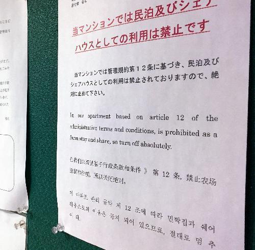 中国系の民泊サイトに掲載されていたマンションには、日本語、英語、中国語、韓国語で「民泊禁止」と書かれた貼り紙があった。住民トラブルも起きている=2017年7月、大阪市内