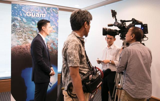 記者会見の後、テレビ局の個別取材を受けるグアムのデナイト観光局長(左)=2017年8月21日、東京都千代田区