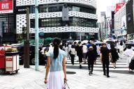 中国からの観光客であふれる銀座の交差点に立つ、中国人の専門ガイドの白樺さん=2017年7月20日