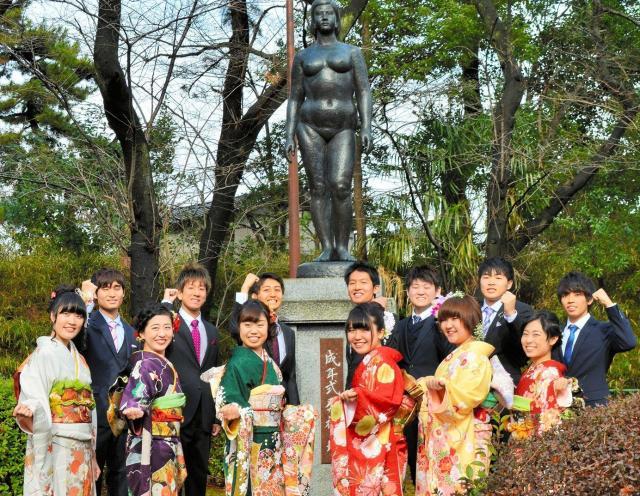 若者の無限の可能性を表したという「成年式発祥の地記念像」の前で記念撮影する新成人たち=2017年1月9日、埼玉県蕨市