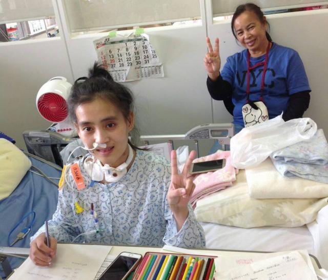 病室でペンを使う練習をするワンウィサさん。後ろはスープンさん