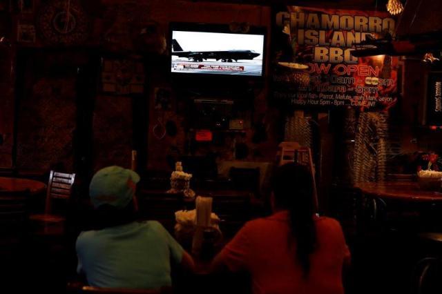 グアムのレストランで、北朝鮮のミサイル発射計画を伝えるテレビニュースを見る地元の住民ら=2017年8月14日、ロイター