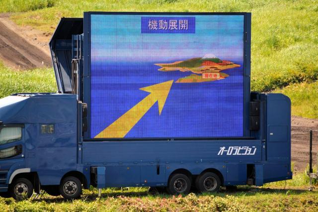 離島奪回訓練を説明する大型モニター=8月27日午前11時45分ごろ、静岡県の陸自東富士演習場