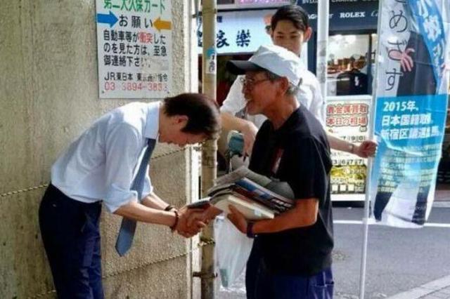 街頭演説で握手をする李さん=新宿区大久保駅前、8月5日