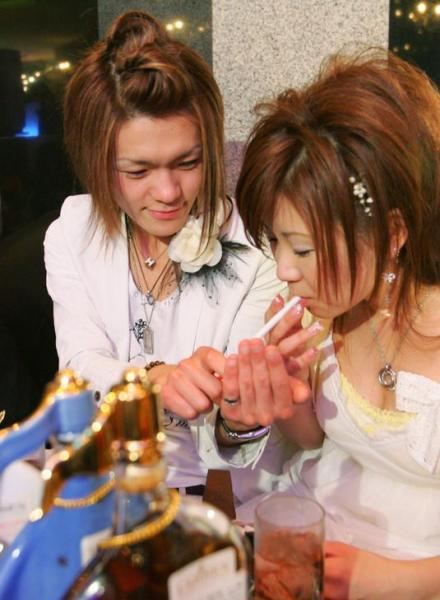 女性客のタバコに火をつけるホストの男性