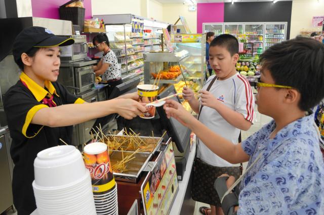 ベトナム・ホーチミンのミニストップでおでんを買う子ども=2015年12月30日、佐々木学撮影